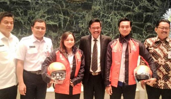 Pelaksana Tugas Gubernur DKI Jakarta Djarot Saiful Hidayat menyerahkan atribut kepada petugas Antar Jemput Izin Bermotor (AJIB) di Balai Agung, Balai Kota Jakarta, 7 Juni 2017.