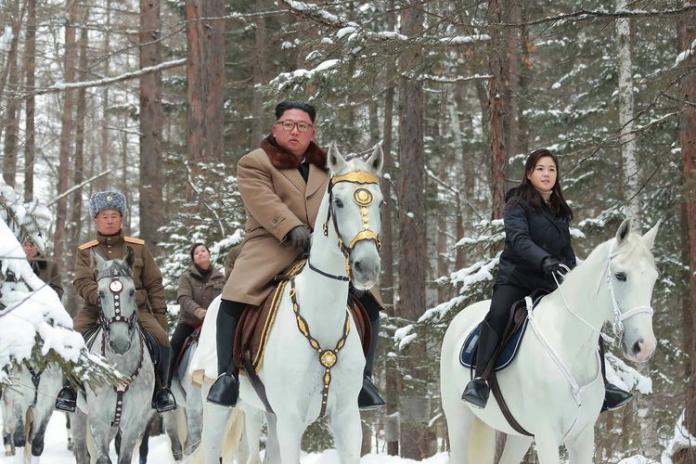 Kim Jong Un (tengah) menunggangi kuda putih berlapis emas ketika berkunjung ke Gunung Keramat Paektu.